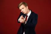 Fotografie confident man showing hand gun gesture on red background