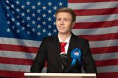 Photo confident emotional man on tribune on american flag background