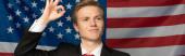 Fotografie smiling man showing ok sign on american flag background