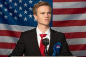 ernster Mann auf der Tribüne vor amerikanischem Flaggenhintergrund