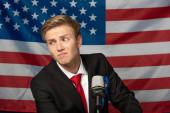Verwirrter Mann auf Tribüne vor Hintergrund amerikanischer Flagge