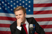 pensive man on tribune on american flag background