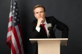 thoughtful emotional man on tribune with american flag on black background