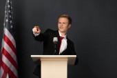 érzelmi férfi ujjal mutogatott kamera tribune amerikai zászló fekete háttér