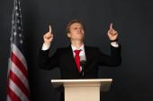 emotivní muž ukazuje prsty nahoru na tribuna s americkou vlajkou na černém pozadí