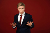 confused man showing shrug gesture on red background