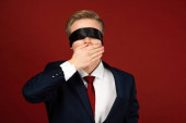 man with blindfold on eyes covering mouth with hand on red background