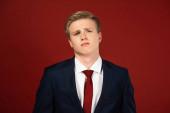 Fotografie Mann mit selbstbewusstem Gesichtsausdruck auf rotem Hintergrund