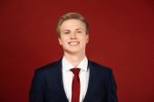 Fotografie Lächelnder Mann im Anzug auf rotem Hintergrund