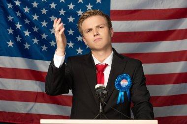 displeased man on tribune on american flag background