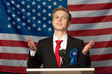 emotional man on tribune during speech on american flag background