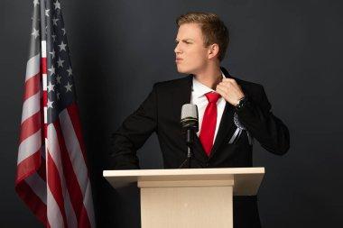 displeased emotional man on tribune with american flag on black background