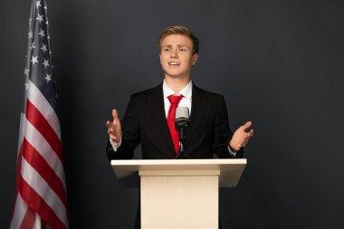 emotional man speaking on tribune with american flag on black background