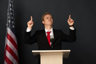 emotional man pointing with fingers upwards on tribune with american flag on black background