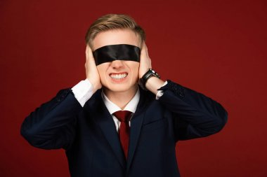Man with blindfold on eyes covering ears with hands on red background stock vector