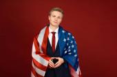 usmívající se muž s americkou vlajkou na červeném pozadí