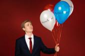 Fotografie Emotionaler Mann mit Luftballons mit Amtsenthebungsbeschriftung auf rotem Hintergrund