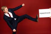 Emotionaler Mann schubst mit Bein weiße Karte mit Impeachment-Schriftzug auf rotem Hintergrund