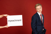 skeptical man grimacing near white card with impeachment lettering on red background