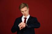 Fotografie Mann schaut auf Armbanduhr auf rotem Hintergrund
