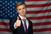 Mann zeigt Daumen hoch auf Hintergrund amerikanischer Flagge