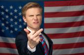 Kyjev, Ukrajina - 18. října 2019: rozzlobený muž napodobující Donalda Trumpa ukazující prostředníček na pozadí americké vlajky