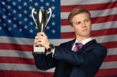 Photo man holding golden goblet on american flag background