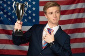 man pointing with finger at golden goblet on american flag background