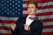 muž ukazuje prsty pryč na pozadí americké vlajky