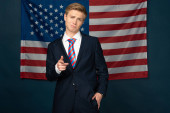 man pointing with finger at camera on american flag background