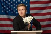 férfi kezében készpénz tribune amerikai zászló háttér