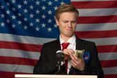 Fotografie Mann mit Bargeld auf Tribüne vor Hintergrund amerikanischer Flagge