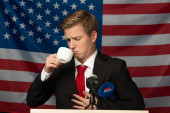 man looking at coffee cup on tribune on american flag background
