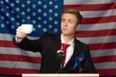 muž při pohledu na šálek kávy na tribune na americkém vlajkovém pozadí