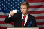 Photo man drinking coffee on tribune on american flag background