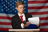 emotivní muž při pohledu na schránku na tribune na pozadí americké vlajky