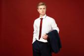 Fotografie Mann mit Hand in der Tasche und Blazer auf rotem Hintergrund