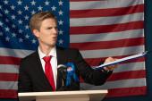 Photo emotional man holing clipboard on tribune on american flag background