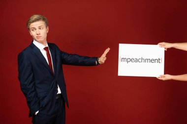 emotional man showing no gesture to white card with impeachment lettering on red background
