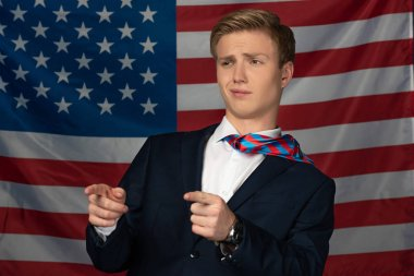 man pointing with fingers away on american flag background