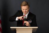 emotional man touching microphone on tribune on black background