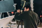 Boční pohled kameramana s fotoaparátem a reflektory na pozadí