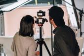 Zadní pohled kameramana a asistenta při pohledu na displej kamery při práci se ženou ve fotostudiu