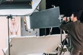 Videograf pracující s krásnou ženou ve fotostudiu