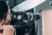 Selektivní zaměření kameramana natáčení krásné ženy ve fotostudiu
