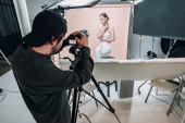 Kameraman při pohledu na displej fotoaparátu při natáčení atraktivního modelu ve fotostudiu