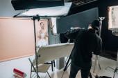 Gyönyörű modell pózol masszázs henger videós fényképezőgép a fotó stúdióban