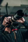 Nízký úhel pohledu kameramana hledícího hledáčkem kamery