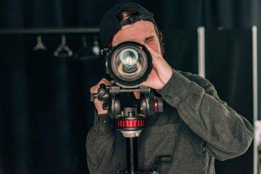 Videographer looking through camera in photo studio stock vector