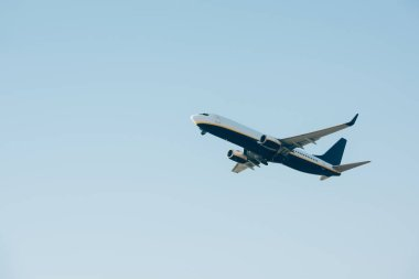 Low angle view of jet liner taking off in blue sky